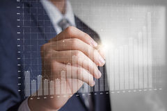 Geschäftsmann zeichnet ein Gewinn-Wachstums-Diagramm lizenzfreie stockfotos