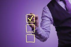 Geschäftsmann zeichnet ein Prüfzeichen im Auswahlrahmen Stockfotografie