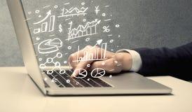 Geschäftsmann-Zeichnungsdiagramme mit Laptop Lizenzfreies Stockfoto