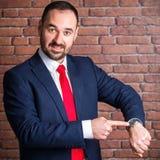 Geschäftsmann zeigt auf die Uhr stockfoto