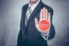 Geschäftsmann zeigt das Stoppschild, das auf der Hand gemalt wird Lizenzfreie Stockbilder
