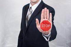 Geschäftsmann zeigt das Stoppschild, das auf der Hand gemalt wird Stockfotografie