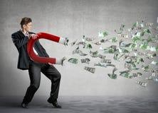 Geschäftsmann zieht Geld an Stockbild