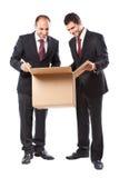 Geschäftsmann zwei, der innerhalb eines Kastens und eines Lächelns schaut Stockfotografie