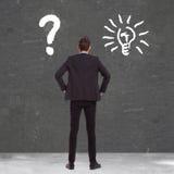 Geschäftsmann zwischen Verwirrung und einer großartigen Idee Lizenzfreie Stockfotos