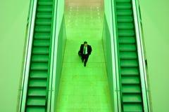 Geschäftsmann zwischen zwei Rolltreppen Stockfoto