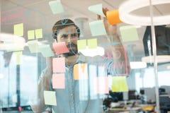 Geschäftsmannanalysieren stratedy auf Glas bei der Anwendung des Handys Stockbild