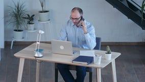 Geschäftsmannarbeit über Computer bei der Unterhaltung am intelligenten Telefon stock video