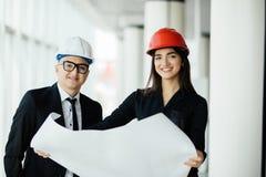 Geschäftsmannarchitekten betrachten PapierplanGeschäftsfrauarchitekten im Büro, um Geschäftsprojekte im Bürogebäude zu besprechen lizenzfreies stockbild