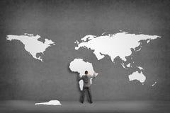 Geschäftsmannattachés zur Wand der Kontinente stockfoto