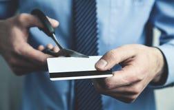 Geschäftsmannausschnittkreditkarte mit Scheren lizenzfreie stockfotos