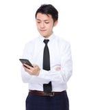Geschäftsmannblick auf das Mobiltelefon Lizenzfreies Stockbild