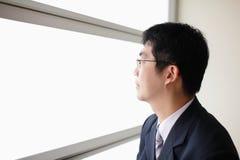 Geschäftsmannblick durch Fenster Stockfotografie
