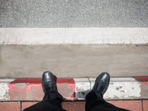 Geschäftsmannblick unten zur Straße Lizenzfreie Stockbilder