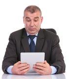 Geschäftsmannblicke überrascht an seiner Tablette Lizenzfreies Stockfoto