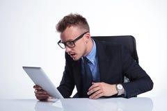 Geschäftsmannblicke entsetzt an der Tablette Lizenzfreie Stockbilder