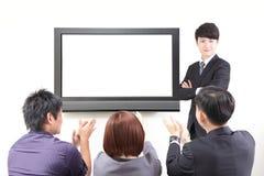 Geschäftsmanndarstellung zu den Kollegen mit Fernsehen Lizenzfreies Stockfoto