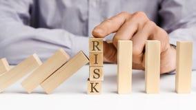 Geschäftsmannenddomino-effekt mit Wort Risiko stockfotografie