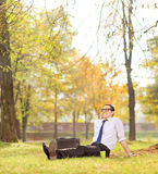 Geschäftsmannentspannung gesetzt auf dem Gras im Park Stockfotos
