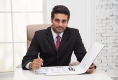 Geschäftsmannexekutivschreibensanmerkungen während lächelnder Blick auf das c Stockfoto