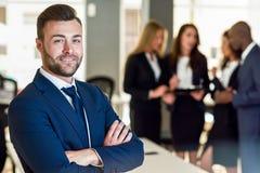Geschäftsmannführer im modernen Büro mit dem Wirtschaftlerarbeiten Stockbild