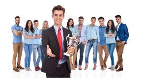 Geschäftsmannführer mit Trophäe Sie mit einem Händedruck grüßend Lizenzfreie Stockbilder