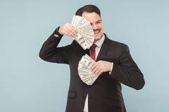 Geschäftsmannfelle hinter Fans aus Geld heraus stockfoto