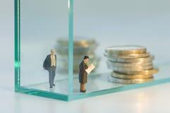 Geschäftsmannfigürchen, die über Altersrente planen Stockbilder