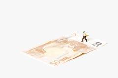 Geschäftsmannfigürchen, die auf einer Eurobanknote läuft Stockfotografie