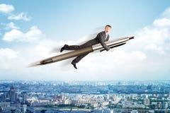 Geschäftsmannfliegen auf großem Stift Stockfotos