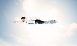 Geschäftsmannfliegen mag einen Superhelden in den Wolken auf dem Himmel Stockbild