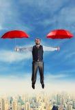 Geschäftsmannfliegen mit Regenschirmen lizenzfreie stockfotos