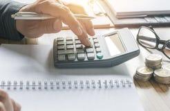 Geschäftsmannfunktion und Anwendung eines Taschenrechners für Geschäft und acco Stockfotos