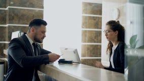Geschäftsmanngast, der mit dem Empfangsdamenmädchen steht am Schreibtisch in der Hotelaufnahme sprechen und Lohnliste mit Kreditk stock video footage