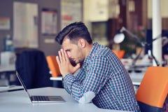 Geschäftsmanngefühlskopfschmerzen, beim Erledigen der Telearbeit in der Kaffeestube ermüdeten mit Ausfall von Plänen stockbilder