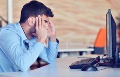 Geschäftsmanngefühlskopfschmerzen, beim Erledigen der Telearbeit in der Kaffeestube ermüdeten mit Ausfall von Plänen stockbild