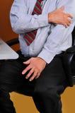 Geschäftsmanngefühlsschmerz in seinem linken Arm Lizenzfreies Stockfoto