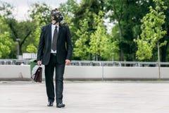 Geschäftsmanngehen im Freien, eine Gasmaske auf dem Gesicht tragend stockfotografie