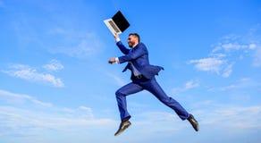 Geschäftsmanngesellschaftsanzugfliege in einer Luft mit Hintergrund des blauen Himmels des Laptops Wunderbar online Unterstützung stockfotografie