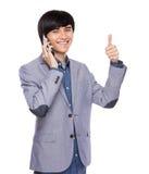 Geschäftsmanngespräch zum Handy und zum Daumen oben Stockbilder