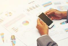 Geschäftsmanngriff ein Smartphone mit DiagrammGeschäftsberichthintergrund Stockbild