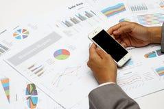 Geschäftsmanngriff ein Smartphone mit DiagrammGeschäftsberichthintergrund Lizenzfreie Stockbilder