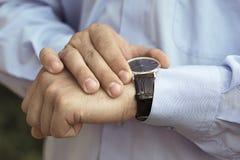 Geschäftsmannhändchenhalten, das auf seine Uhr aufpasst Stockbild