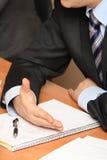 Geschäftsmannhände und -notizblock Stockbild