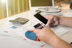 Geschäftsmannhände unter Verwendung des Smartphone und der halten Kreditkarte mit Lizenzfreies Stockbild