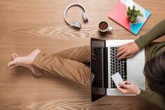 Geschäftsmannhände unter Verwendung eines Laptops mit einem Tasse Kaffee und intelligentes Lizenzfreies Stockfoto