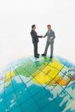 Geschäftsmannhand, die auf dem globalen rüttelt Lizenzfreie Stockfotografie