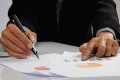 Geschäftsmannhand, die auf Geschäftsdokument während der Diskussion auf das Treffen zeigt stockbild