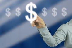 Geschäftsmannhand, die auf Symbolgeld des Dollars in Ihrer Arbeit zeigt Stockbilder