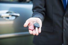 Geschäftsmannhand, die Autoschlüssel zeigt Lizenzfreies Stockfoto